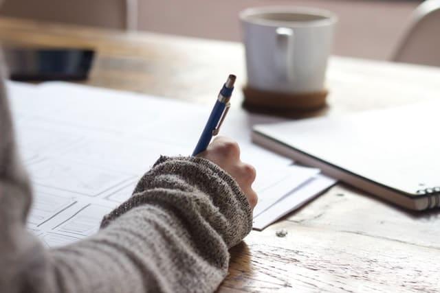 Personne écrivant sur un carnet